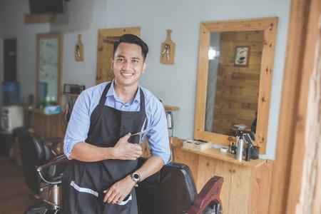 Glückliche junge Besitzer Geschäft in die Kamera schaut, während auf dem Stuhl lehnt an seinem Friseurladen