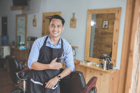 Happy young business owner looking at camera while leaning on chair at his barbershop