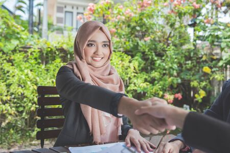 business people meeting: confident young muslim business woman shaking hands. teamwork deal concept Stock Photo