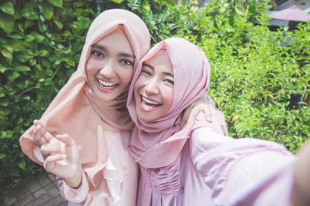 selfie を一緒に取る若いイスラム教徒の女の子の友人を興奮して屋外 写真素材