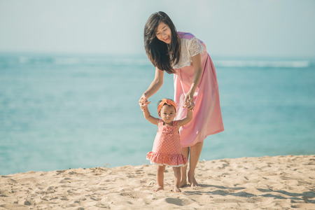 Mother teaching baby to walk on sand. summer fun at the beach