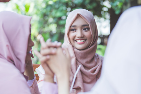 speak out: portrait of pretty asian muslim woman having fun in cafe together with friends Stock Photo