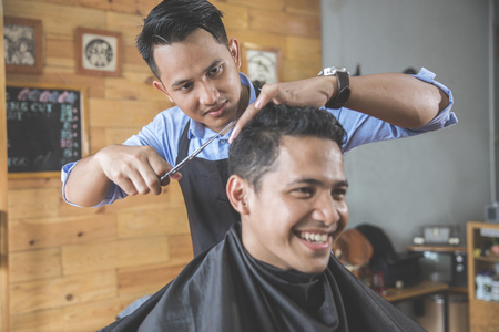 horizontal haircut: portrait of Young handsome barber making haircut of attractive man in barbershop