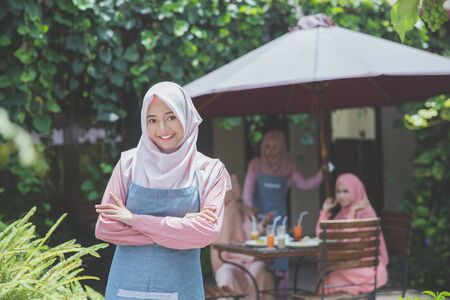 portrait of proud muslim business owner standing in front of her cafe. customer sitting at the background Stock Photo