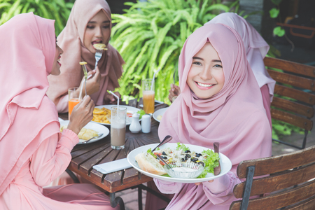 Young cheerful asian girl friends having fun together while having lunch