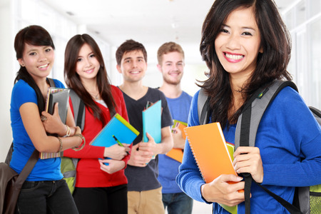 ethnic woman: portrait of pretty young student smiling to camera with friends. unity in diversity on school Stock Photo