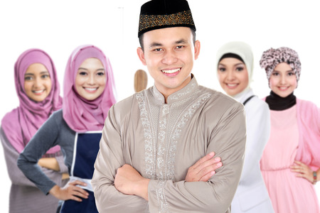muslim male smiling. group of woman with head scarf standing at the background photo