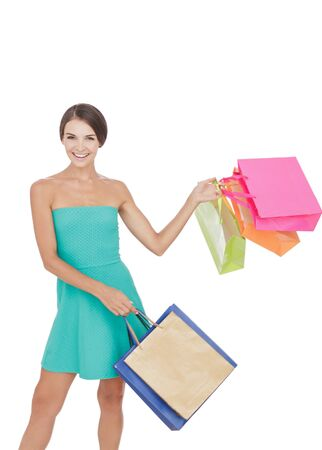 portrait of happy young shopping girl swinging shopping bag isolated on white background