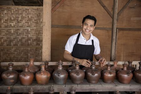 pottery: portrait of Smiling male potter holding his product in pottery workshop