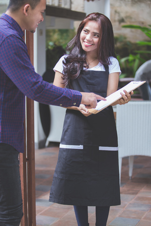 portrait of waitress standing at the front of a cafe inviting people to come in
