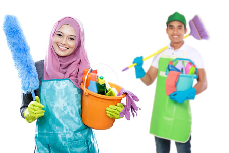 attractive muslim housewife ready to do the chores. housework cleaning concept. male with cleaning tool at the background