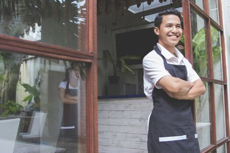 entrepeneur: portrait of young asian male cafe worker smiling to camera