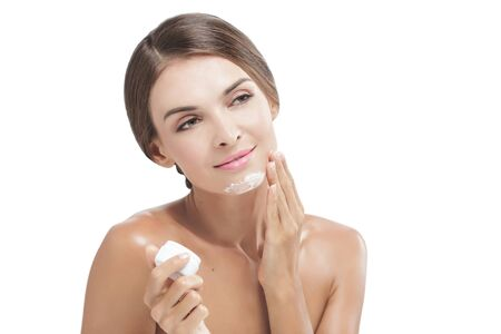 adding: portrait of beautiful young woman applying some facial cream isolated on white background with copy space