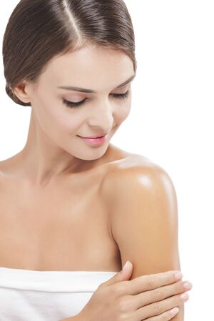 portrait of beautiful woman applying body lotion to her arms isolated on white background