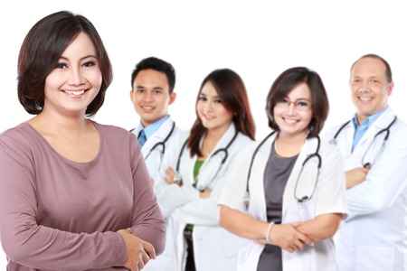 portrait of happy proud patient standing in front a group of doctor photo