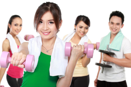 male and female friends doing exercise together at the gym using dumbbell photo