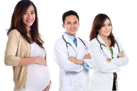 attractive pregnant asian woman standing in front of her doctor photo