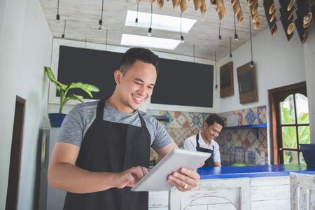 タブレットでアジアの若い男性のカフェのオーナーの肖像画