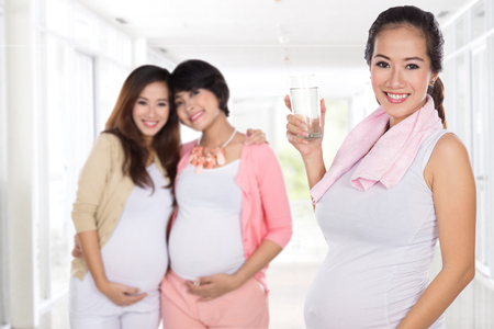 pregnant asian woman having a glass of water after doing some exercise. friends at the background Imagens