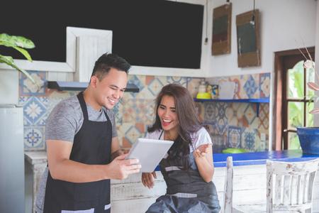 작업하는 동안 태블릿 pc를 사용 하여 두 젊은 카페 작업자의 초상화 스톡 콘텐츠