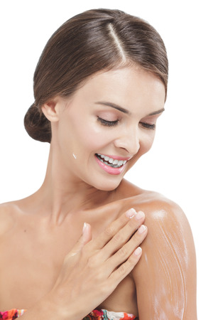 body lotion: portrait of beautiful woman applying body lotion to her arms isolated on white background