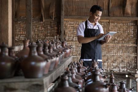 Portret van mannelijke pottenbakker met behulp van digitale tablet in pottenbakkerij. de verkoop van zijn product online