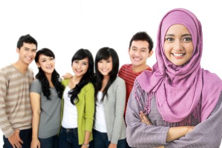 幸せな若いアジア女性着用ヘッド スカーフ バック グラウンドで彼の友人の肖像画