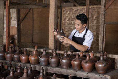 portrait of Smiling male potter holding his product in pottery workshop