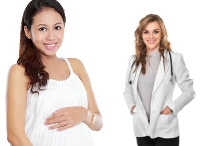 attractive pregnant asian woman standing in front of her female doctor Stock Photo