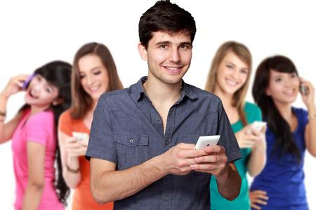 apuesto joven atractivo que usa el teléfono móvil. cuatro diverso origen étnico mujer en el fondo Foto de archivo