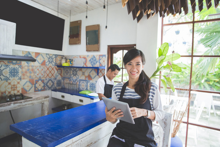 portrait of young attractive cafe owner with tablet
