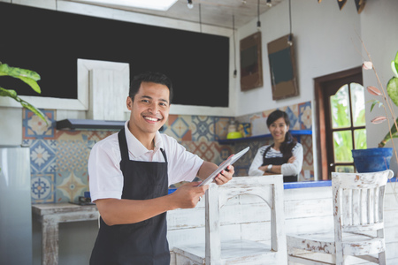 Portrait of smiling male waitress using digital tablet in cafe. his working partner at the background