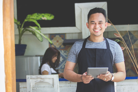 Portrait of smiling male waitress using digital tablet in cafe