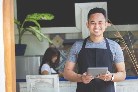 Portret van lachende mannelijke serveerster met behulp van digitale tablet in cafe