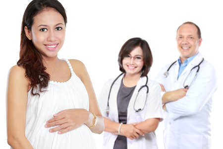 attractive pregnant asian woman standing in front of her male and female doctor photo