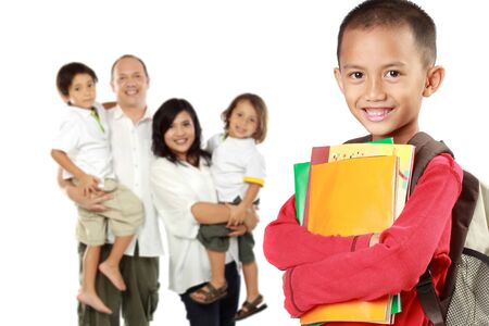 portrait of happy elementary student with books and his family at the background supported him photo