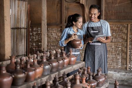 Portret van mannelijke en vrouwelijke potter met behulp van digitale tablet in pottenbakkerij. de verkoop van hun product online Stockfoto - 69607789