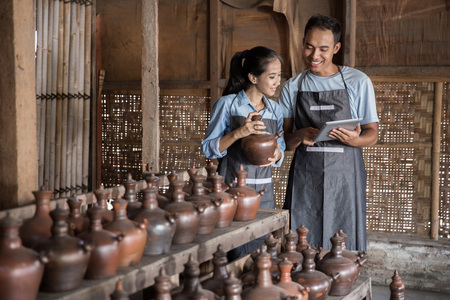 Portrait of male and female potter using digital tablet in pottery workshop. selling their product online Foto de archivo