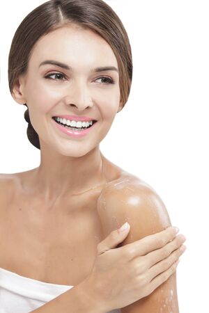 body lotion: portrait of beautiful woman applying body lotion to her arms while smiling isolated on white background Stock Photo