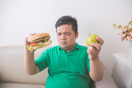 portrait of a man being confused choosing what to eat between healthy fresh fruit or unhealthy junk food