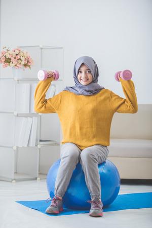 アジアの女性の家庭での運動を行うヘッド スカーフでダンベルを使用してください。