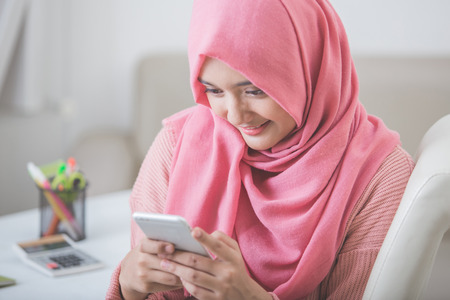 ソファに座りながら携帯電話を使用して幸せなアジア女の肖像