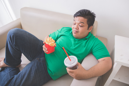 Portrait of lazy obese person eats junk food while laying on a couch Stock fotó