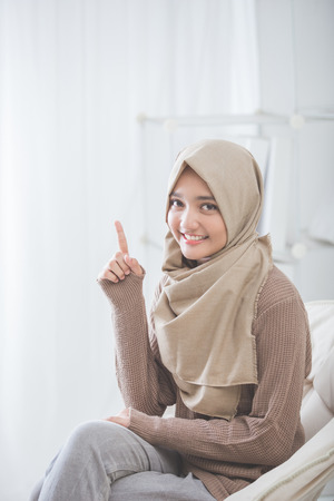 portrait of attractive young woman with hijab smiling presenting to copy space