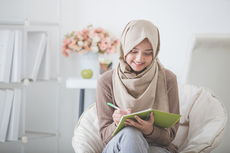 portrait of beautiful asian woman with head scarf writing something