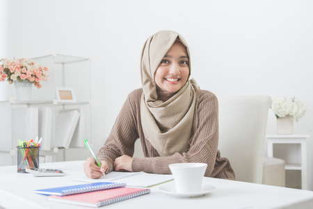 portrait of beautiful female asian student with hijab doing homework Stock Photo - 73465214