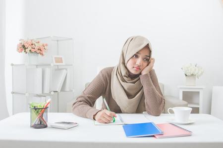 아시아 여성 학생 hijab와 함께 숙제를 피곤