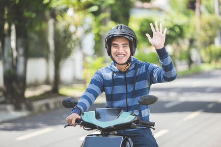 happy asian man waving hand while riding on motorbike in city street