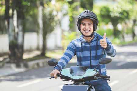portrait of happy asian man riding on motorbike in city street and showing thumb up