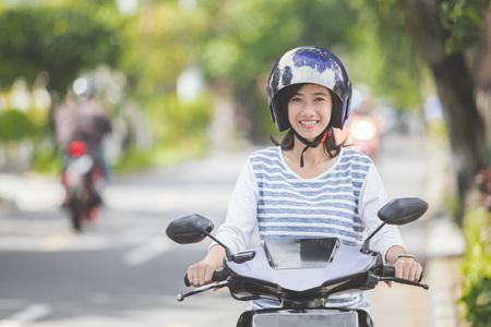 portrait of happy asian woman riding on motorbike in city street